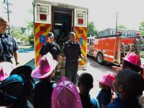 firefighters and emergency medical professionals speaking to kids at a firestation