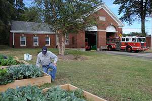 gentlemen tending to vegetable gardens outside a fire station